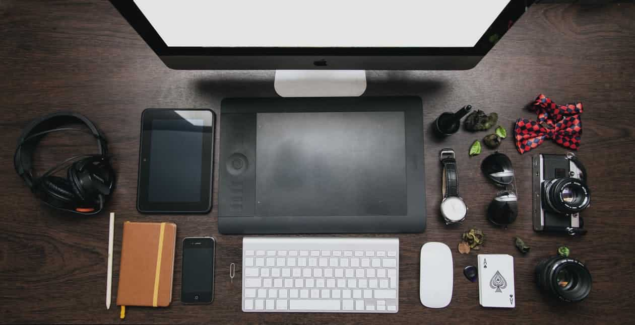 A desk with computer and web designs on